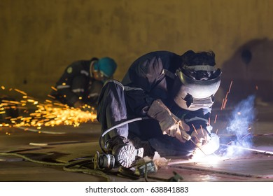 Male two worker wearing protective clothing and repair grinding  storage tank bottom plate inside confined spaces.