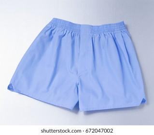 male underwear: blue boxer short over silver background