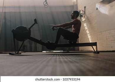 Male using rowing machine at fitness club. Young man doing exercises on fitness machine in gym. Side view.