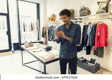 Male using smartphone in fashion shop
