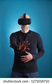 Male using VR Virtual Reality headset on blue background.