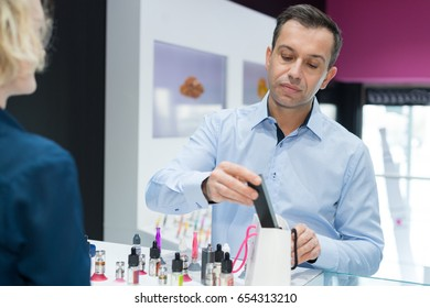male vaping store owner selling electronic cigarette to female client
