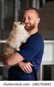 Male veterinarian holds dog in his arms and laughs, dog licks people face.