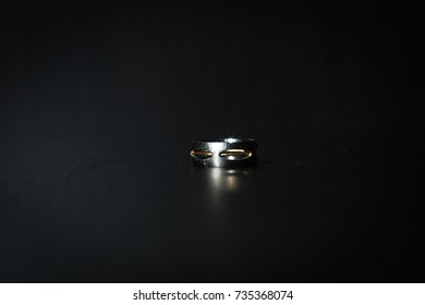 Male vintage brutal silver ring with a thin gold wire on a dark background with a beautiful light pattern