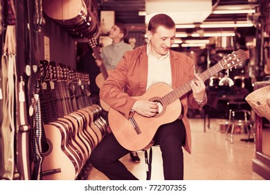 Male visitor examining various acoustic guitars in musical shop