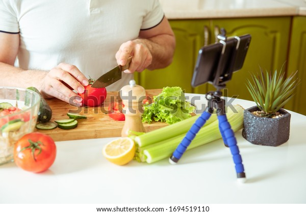Male vlogger recording healthy vegetable recipe. Culinary blog for vegetarians