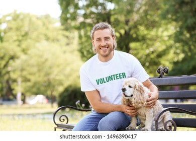 Male volunteer with cute dog sitting on bench outdoors
