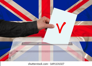 male voter drops a ballot in a transparent ballot box against the backdrop of the Great Britain national flag, concept of state elections, referendum