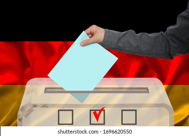 male voter drops a ballot in a transparent ballot box against the background of the national flag of Germany, concept of state elections, referendum
