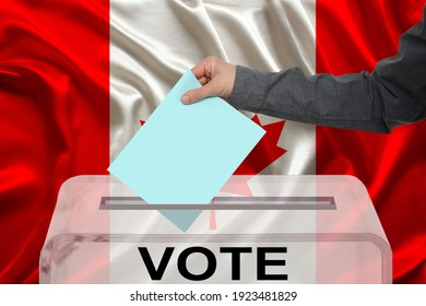 male voter drops a ballot in a transparent ballot box against the background of the national flag of Canada, concept of state elections, referendum