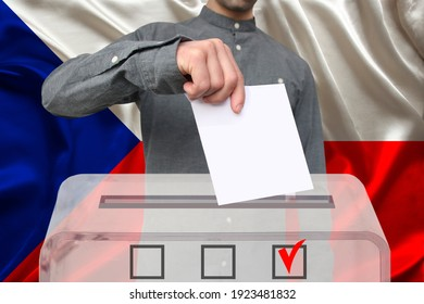 male voter lowers the ballot in a transparent ballot box against the background of the national flag of the country of Czech Republic, concept of state elections, referendum