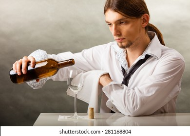 Male waiter or butler serving pouring wine into glass.