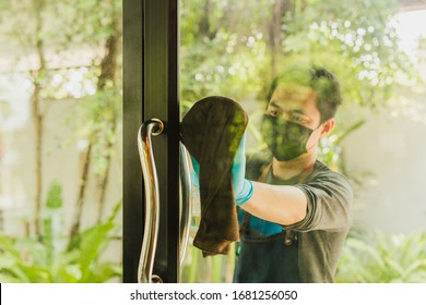 Male waiter cleaning the door glass with cloth and spray bottle at cafe.