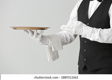 Male waiter with empty tray on grey background