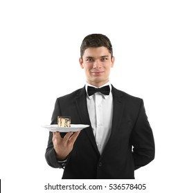 Male waiter holding plate with cake on white background