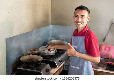 the male waiter smiles with a thumbs up while frying side dishes for customers at the stall