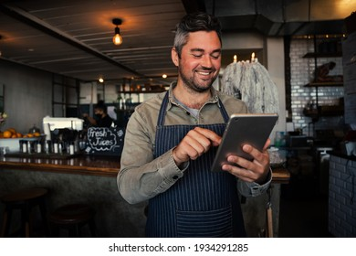 Male waiter smiling while receiving monthly salary on digital tablet in trendy cafe