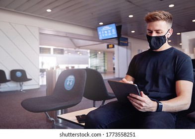 Male waiting in empty airport wearing protective face mask using technology.
