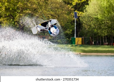 Male wakeboarder jumps over spray on pond in park