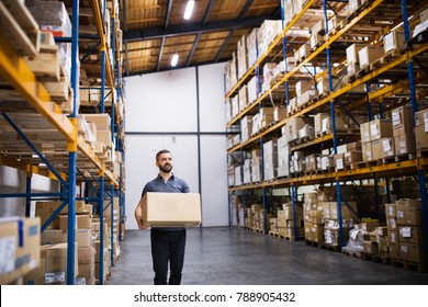 Male warehouse worker with a large box.