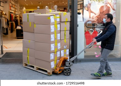 A male warehouse worker loading boxes outside of retail shop in Brussels, Belgium on May 11, 2020
