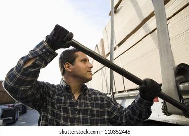Male warehouse worker loading wood on a trailer