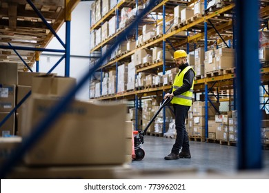 Male warehouse worker pulling a pallet truck.