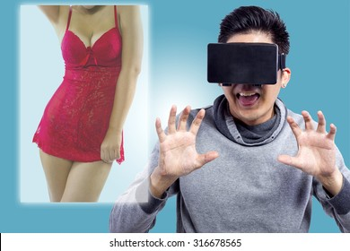 Male watching 3D virtual reality sexy movie with headset.  The man is doing lustful gestures and the female model face if obscured.