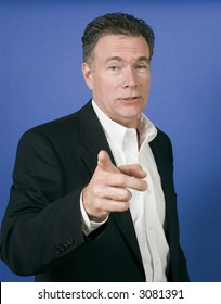 male wearing a black suite gesturing with his finger as if ready to launch into a discussion