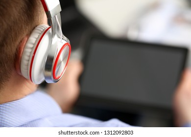 Male wearing headphones wired to pc pad in arms at home closeup. Stock market trade and investment interactive data search wifi connection wireless ip telephony inspiration idea web social network