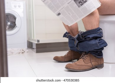 Male wearing jeans and shoes reading newspaper while sitting on the toilet seat in  the modern tiled bathroom at home