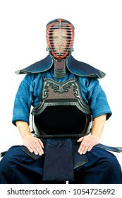 Male wearing a kendo armor with helmet, sitting position.
