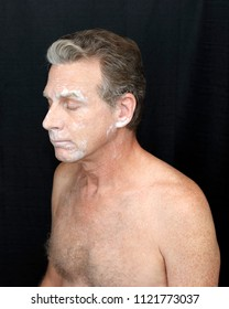 Male wearing a light bentonite clay treatment mask. Thin bentonite clay face treatment worn by a guy. Thin white bentonite clay beauty treatment of mature shirtless man on black cloth curtain backdrop