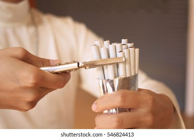 Male wears white t-shirt and Iron Necklace/has  Locking Pliers in hand /  stops smoking ,no smoking,Cigarette is dangerous concept World No Tobacco Day