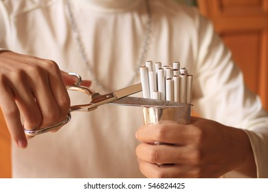 Male wears white t-shirt and Iron Necklace/cut cigar with scissors/  stops smoking ,no smoking,Cigarette is dangerous concept World No Tobacco Day