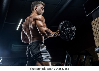 Male weightlifter, training in the gym, dumbbells. training, difficult coaching. Sports nutrition.
