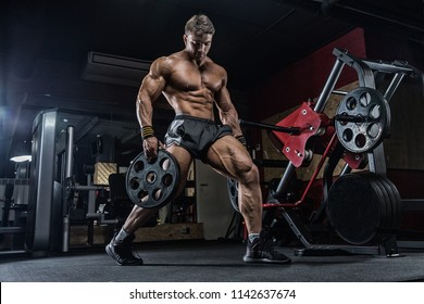 Male weightlifter, training in the gym, dumbbells. Crossfit training, difficult coaching. Sports nutrition.
