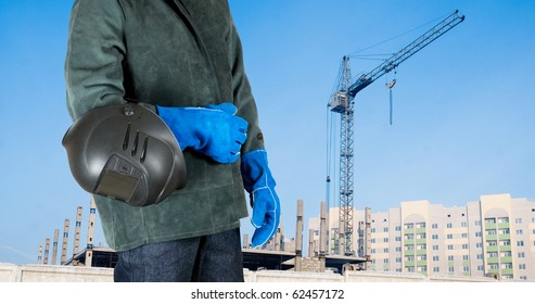 male welder closeup with welding equipment on building background