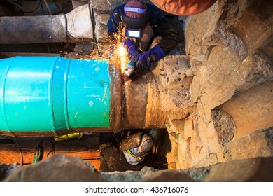 Male welder worker wearing protective clothing fixing Repair Pipeline welding and grinding industrial construction oil and gas or  pipeline inside confined spaces.