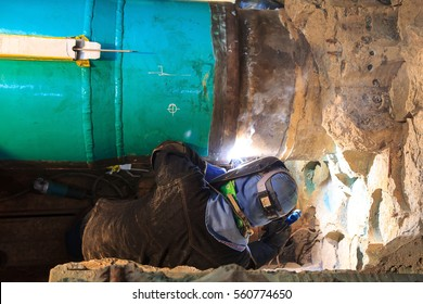 Male welder worker wearing protective clothing fixing Repair Pipeline welding industrial construction oil and gas or  pipeline inside confined spaces.