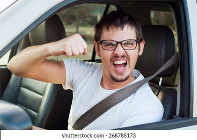 Male white angry driver is showing his fist and mad face