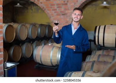 Male winemaker in uniform having glass of wine in hands in cellar