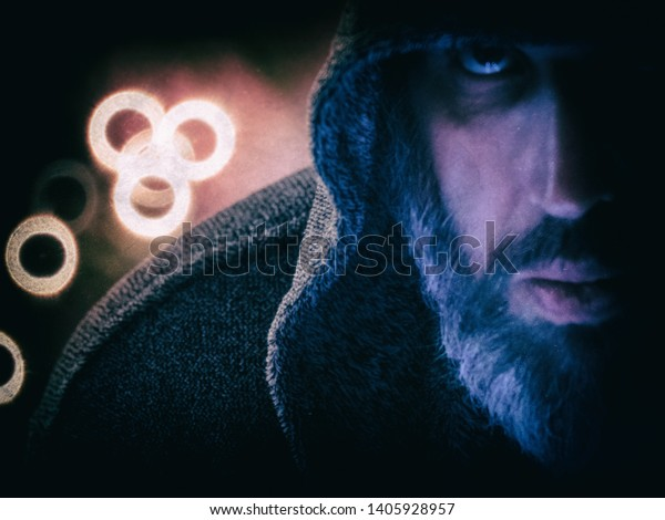 A male wizard  wearing a hood and standing in front of ring boke