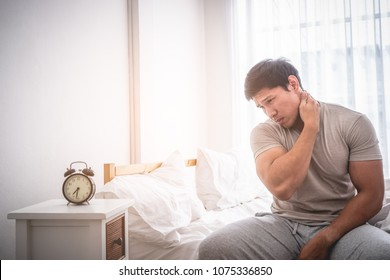 Male woke up by alarm clock having neck pain from sleeping, Tired Man had a sleepless night or Hangover and have to wake up early morning.