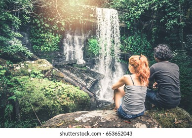 Male and woman couples asia. Walking hand travelers travel nature Forests, mountains, waterfalls. puhinrongkla romklao-paradorn waterfall