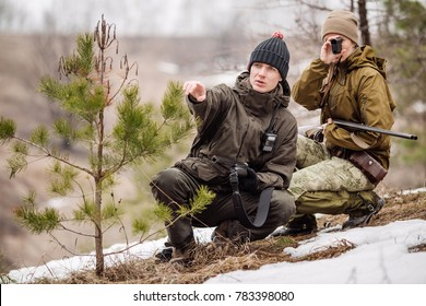 male and woman hunters ready to hunt, holding gun and walking in forest. hunting and people concept