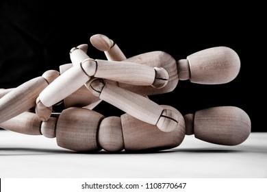male wooden doll lie above feminine mannequin . night scene
