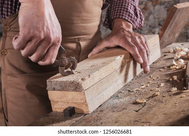 Male woodworker using metal plier tool to chip pieces off of block while he holds it against wooden table