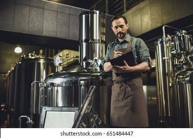 Male worker in apron inspecting industrial equipment and making notes at the brewery