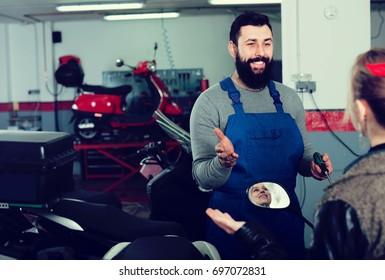 male worker assisting blonde female customer in repairing motorcycle in workshop